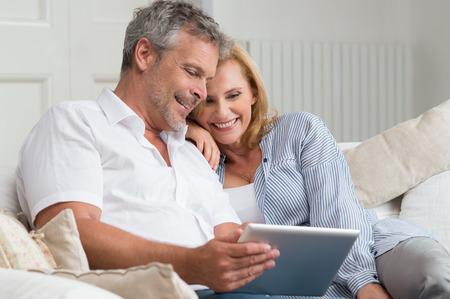 31178955 - happy mature couple sitting on sofa with digital tablet